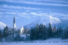 Blick über die Kirche Maria Himmelfahrt zum schneebedeckten Wallberg